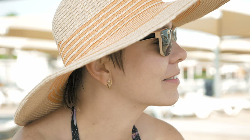 A woman is shown at the beach with style attire. One can still be fashionable and in trend while traveling. A nice pair of sunglasses completes the look. | Shutterstock HD Video #18477886