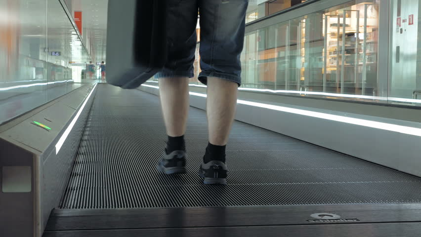 4k00:20A Person Is Walking On A Moving Pathway In The Airport. It Is Used  To Transport People Across Hall. Travolator Makes Is Easy To Carry Heavy  Luggage.
