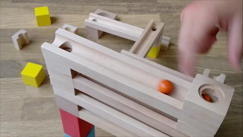 Ball track line with three marbles rolling down on wooden toy track