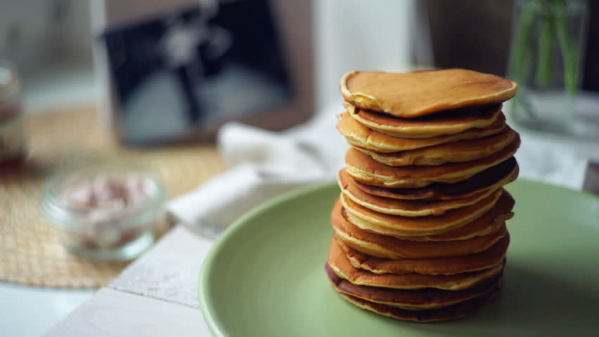 Kitchen Table Close Up pancakes stack on green plate at kitchen table. close up of sweet