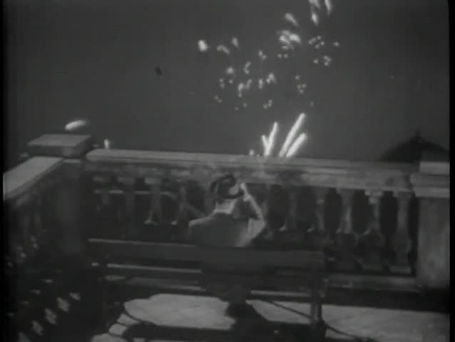 Rear view of man on bench watching fireworks from terrace