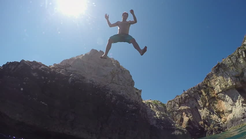 SLOW MOTION UNDERWATER: Happy young man with hands raised jumping into water off a rocky wall at sunny seaside. Fearless guy on fun summer vacation diving into refreshing sea off extremely high cliff