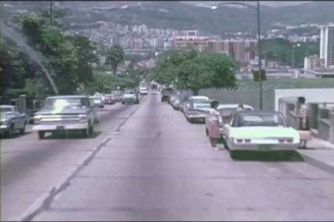 Downtown Caracas in 1973, Venezuela, museums, and city parks, with a motorist\xEAs POV driving to another section of the city, on a two lane highway along the coast. (1970s)