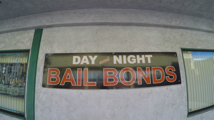 BURBANK, CA/USA: February 21, 2016- A close up shot of a Bail Bonds Business sign on a window in Burbank California. The reflection of traffic can be seen passing by. | Shutterstock HD Video #18538238