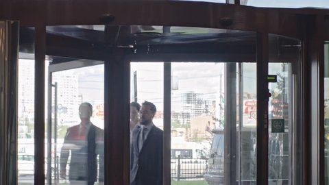Businesswoman and her two businessmen entering office building through glass revolving door and looking around
