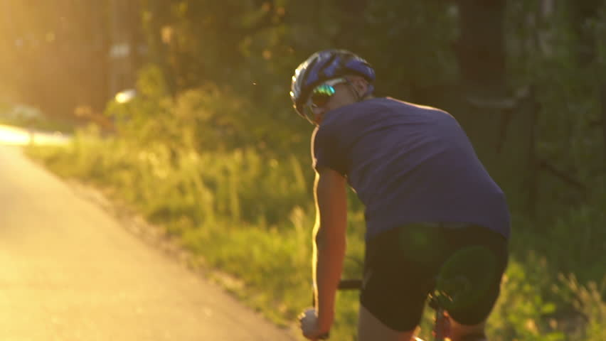 Young man Cyclist on road bike in sunset. Cycling. Slow motion #18557636