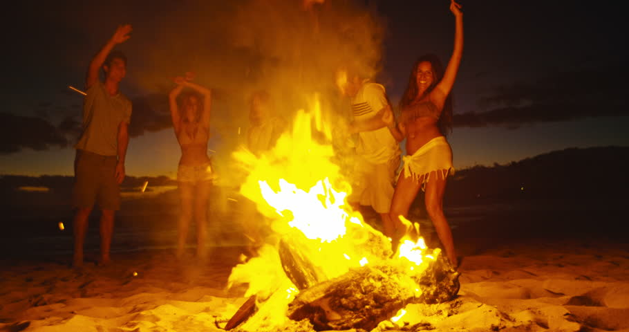 Group of friends dancing around bonfire on the beach at sunset