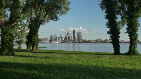 A cinematic tracking shot of Louisville and the Ohio River as the camera moves past beautiful green trees on an open grassy field straight toward the heart of the city on the other side of the water.