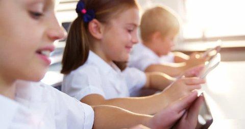 School kids using digital tablet in classroom at school 4k