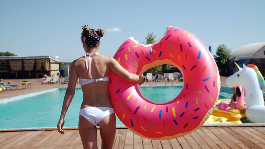Woman in pink bikini jumping into swimming pool in slow motion. 20s. 1080p Slow Motion.