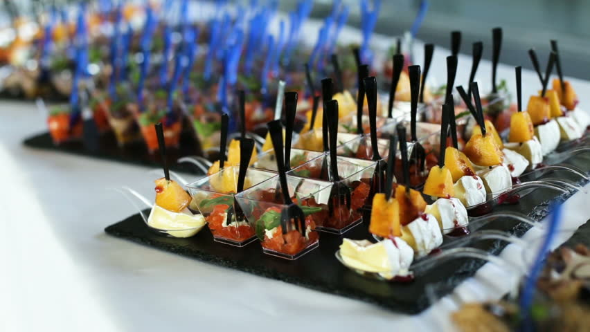Man grabs appetizers from a cocktail hour spread.