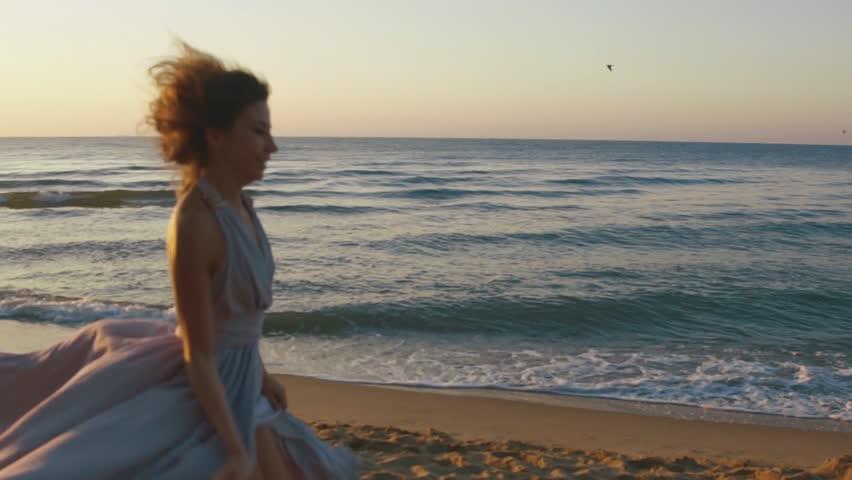 Young charming girl in long light pink dress playfully runs along coastine on sandy beach with golden sunset lights | Shutterstock HD Video #18656618
