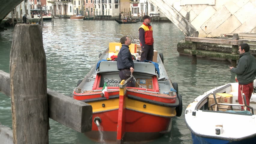 VENICE, ITALY - FEBRUARY 24 2009 Postman on a boat on the Canale Garnde 24th of
