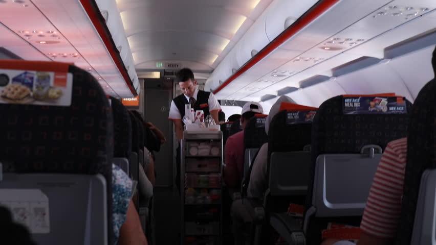 Barcelona, Spain - Circa June 2016- Flight attendant selling food on flight. Passenger buying food on flight. Plane flight interior | Shutterstock HD Video #18688151