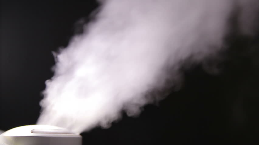 Humidifier emits smoky vapors in dark room at night.