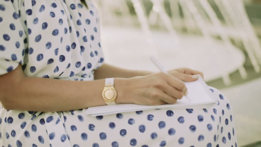 A woman writing. Closeup. A middle aged woman in a big white hat writing a letter with a white pen on paper near fountain.