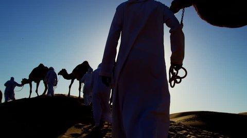 Camel caravan train travelling across a Middle Eastern desert