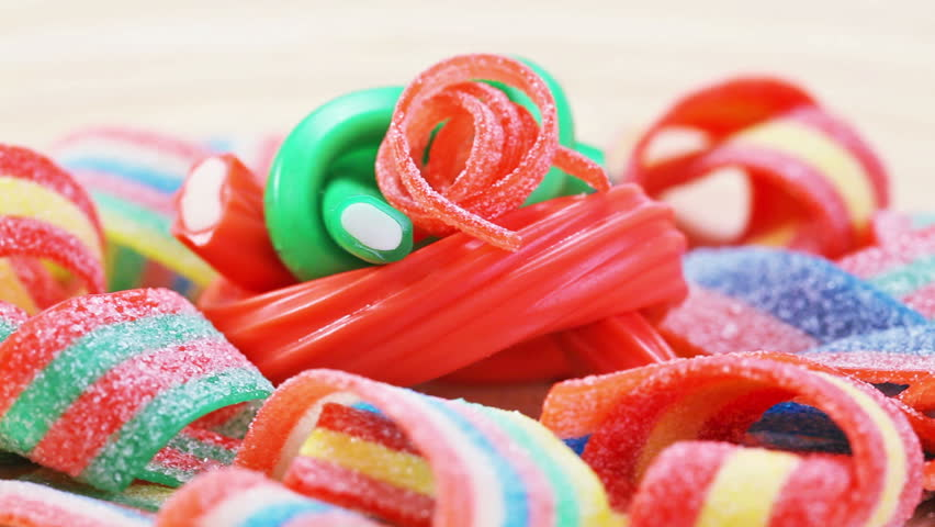 Colorful gummy candy (licorice) rotating sweets background, closeup view
