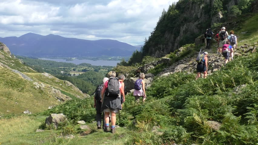 Big group of senior people with backpacks and walking poles hiking in picturesque Cumbria, Lake District, England.Slow motion