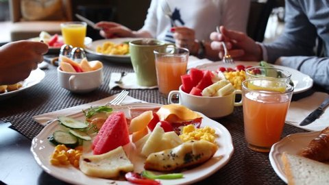 Table with food and glasses of juice, hands of eating people