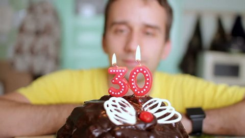 Man blows out the candles 30 years on a chocolate cake with butterfly wings. The man has a birthday today.