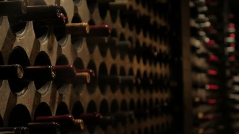 Close-up focus pull of wine bottles in a vintage Victorian gothic revival style wine cellar