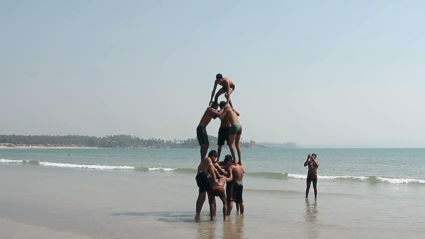 Goa, India - February 17, 2016: Happy man making human pyramid on the Palolem beach
