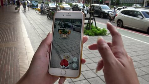Taipei, Taiwan-06 August, 2016: 4K Playing Pokemon Go on App in Asia city street. Asian woman holds a smart phone showing on screen the augmented reality mobile game. Catching a Krabby creature -Dan
