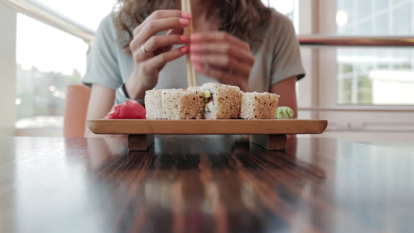 Young woman in cafe eating sushi with chopsticks | Shutterstock Video #18850388
