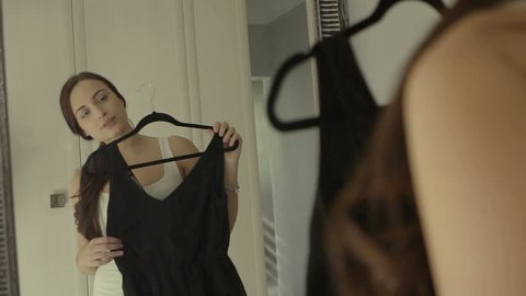 Clothing, wardrobe, fashion, style and people concept - happy brunette woman with black dress on hanger at mirror at home