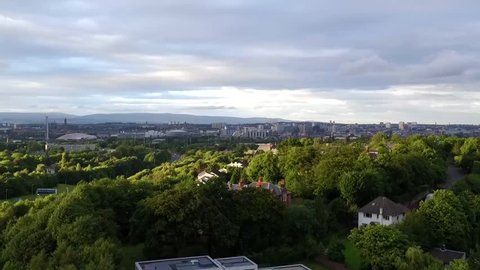 Aerial view of Glasgow city at sunset from the suburbs. Drone rises from residential area in foreground to reveal Glasgow city in the background.  Sunset lit houses and trees in foreground.