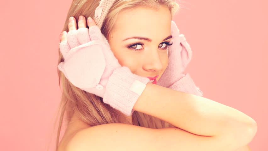 Happy smiling blonde woman in pink winter mittens and earmuffs on pink studio background