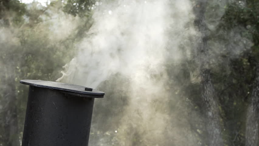 slow motion smoke from an outdoor BBQ pit or grill