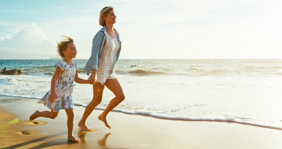 Mother and daughter having fun walking and playing on the beach at sunset | Shutterstock HD Video #18944168