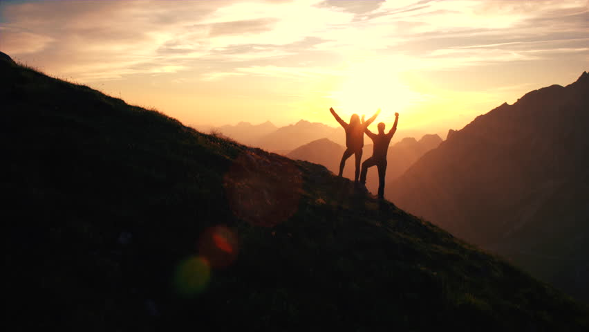 Aerial, edited - Rising above hiking couple celebrating successful climb on the mountain with raising arms at beautiful sunset