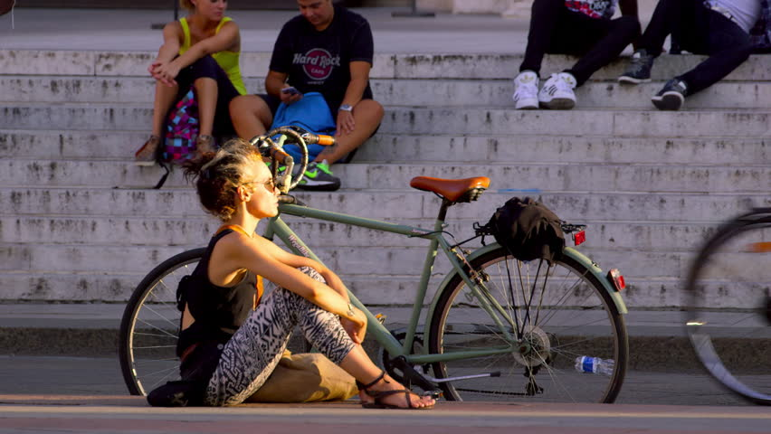 ITALY, BOLOGNA - SEPTEMBER 2015: Woman Sitting In The Sun Near Bicycle; Piazza Maggiore Bologna