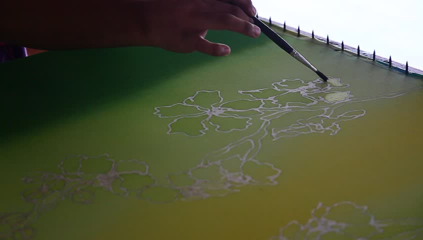 An artist carefully paint the floral/flower motif on a yellow traditional batik fabric