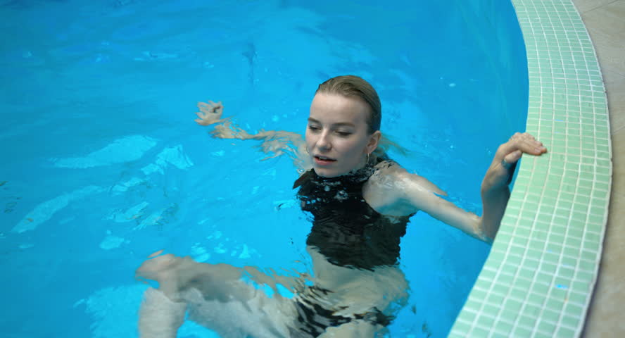 Beautiful young girl relax in the pool. She is very sexy. 4K steadicam shot.