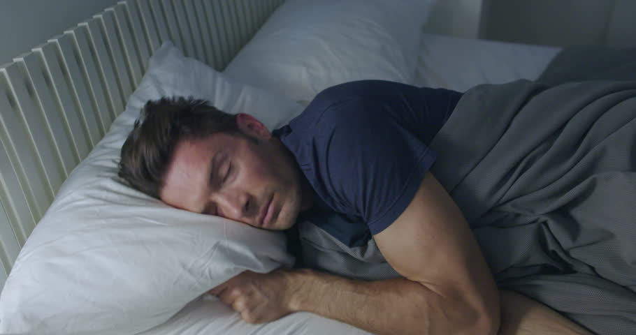 Sleeping man turns towards light while dreaming in a double bed with soft ambient light.  Camera move on jib arm.  Side view, medium shot.