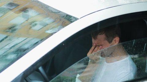 sad man crying in the car. rain on the street. man in hysterics