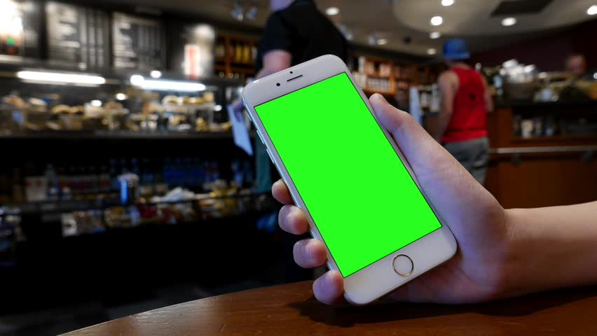 Port Coquitlam, BC, Canada - July 28, 2016 : Hand holding green screen iphone inside Starbucks store with 4k resolution.