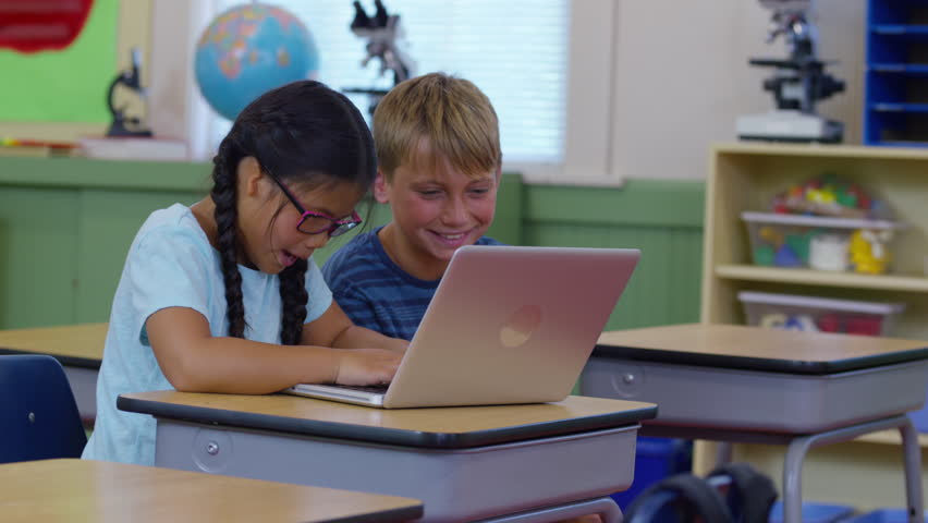 Two kids in school classroom working on laptop computer | Shutterstock HD Video #19004401