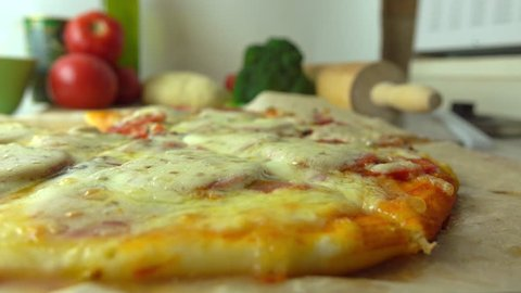 Cooking, part of the set. Taking a piece of freshly baked homemade pizza with stretching cheese. 4K close up video