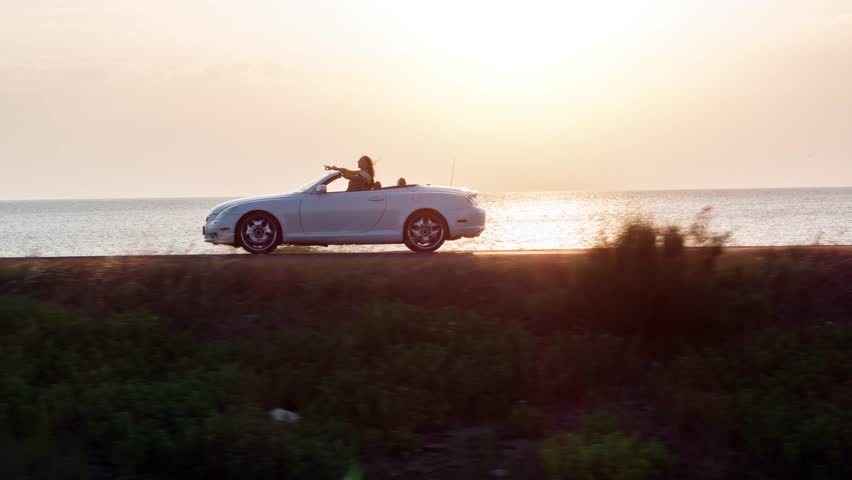 Man And Woman Driving Convertible Car By The Beach At Sunset Vacation Girl Happy Wind Blowing Hair Summer Joy Holiday Happiness Romantic Couple Honeymoon Concept Drone Aerial | Shutterstock HD Video #19037458