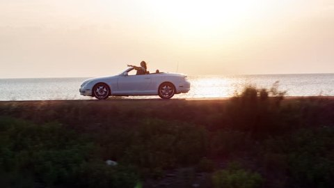 Man And Woman Driving Convertible Car By The Beach At Sunset Vacation Girl Happy Wind Blowing Hair Summer Joy Holiday Happiness Romantic Couple Honeymoon Concept Drone Aerial