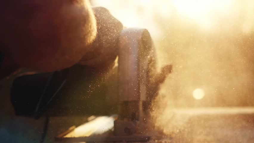 Man is craft working at a work bench with power tools in slowmotion during sunset with beautiful lens flare. 1920x1080 | Shutterstock HD Video #19061548