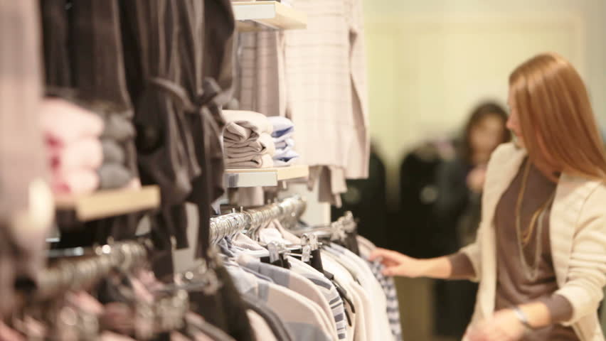 Attractive blond girl choosing a striped pullover in the mall | Shutterstock HD Video #1906309