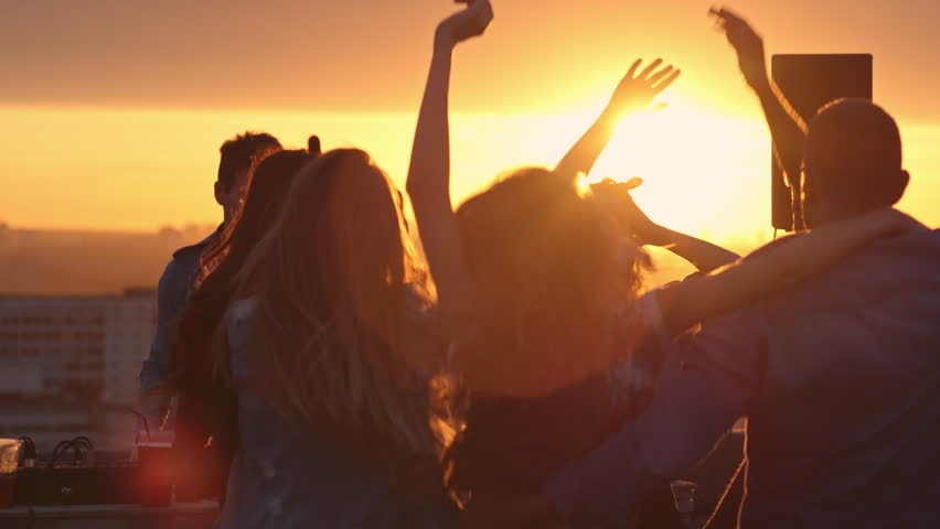 Group of diverse young people dancing with raised arms to the music played by dj at rooftop party at sunset
