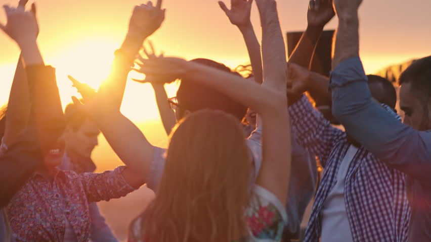 Group of young multi-ethnic people dancing with raised arms to the music played by dj at rooftop party at sunset