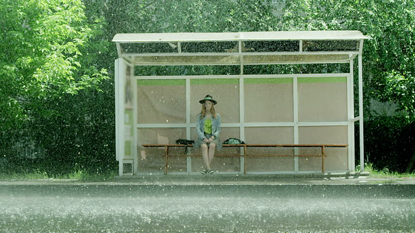 Girl sitting at the bus stop in the rain.  Shot on RED EPIC Cinema Camera in slow motion.